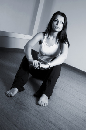 A girl with long black hair sitting on the floor