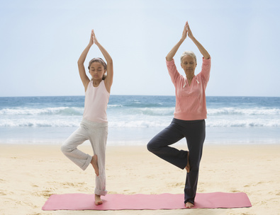 Grandmother and granddaughter practicing yoga on beach